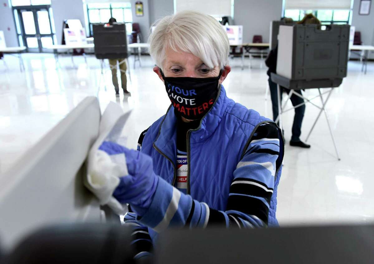 Cheshire Assistant Registrar of Voters Madalyn Yerkes sanitizes voting booths after each usage in the cafeteria of Cheshire High School on November 3, 2020.