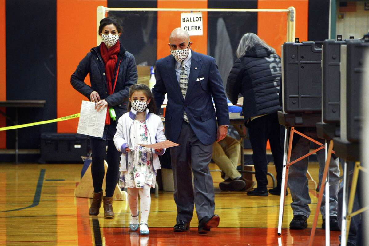 State Rep. Jason Perillo (R-113) is joined by his daughter, Lydia, as he and his wife, Becky, prepare to vote on Election Day at Shelton Intermediate School, in Shelton, Conn. Nov. 3, 2020.