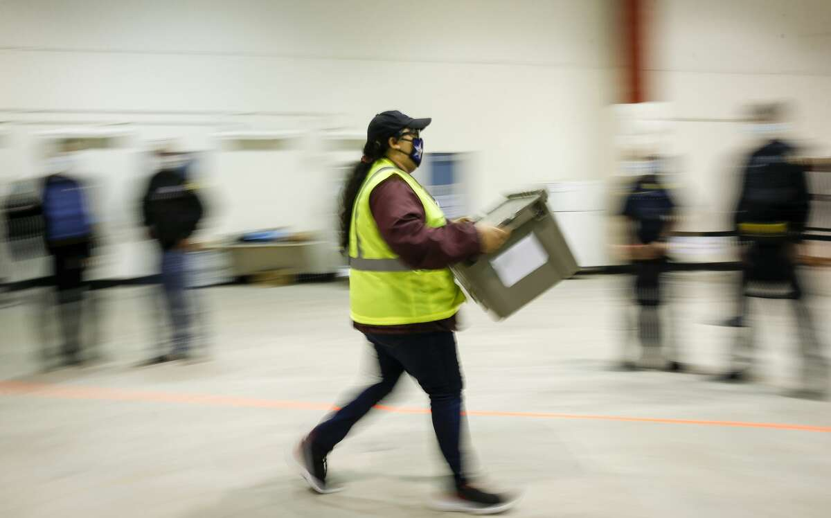 Election workers carry election materials Tuesday, Nov. 3, 2020, at NRG Arena in Houston.