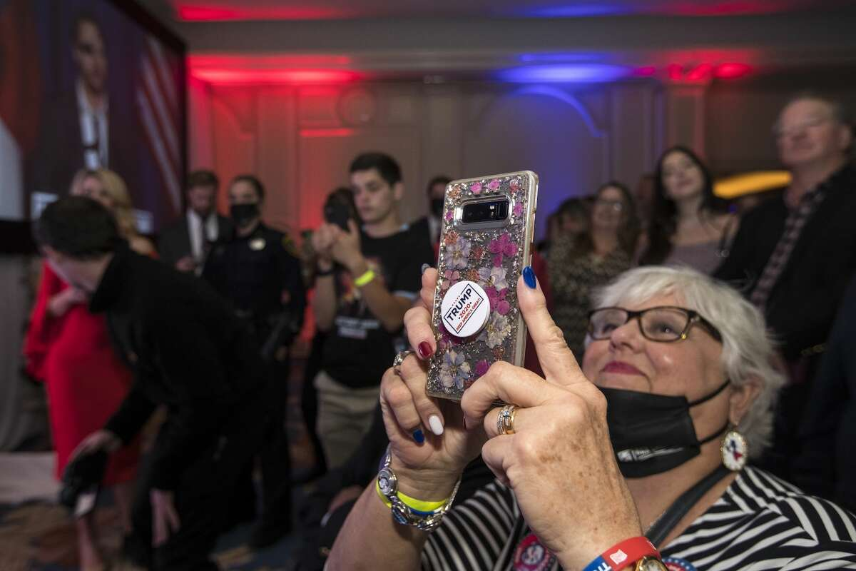 Supporters of Republican congressman Dan Crenshaw watch him speak as he celebrates his victory during an election watch party Tuesday, Nov. 3, 2020 in Houston.