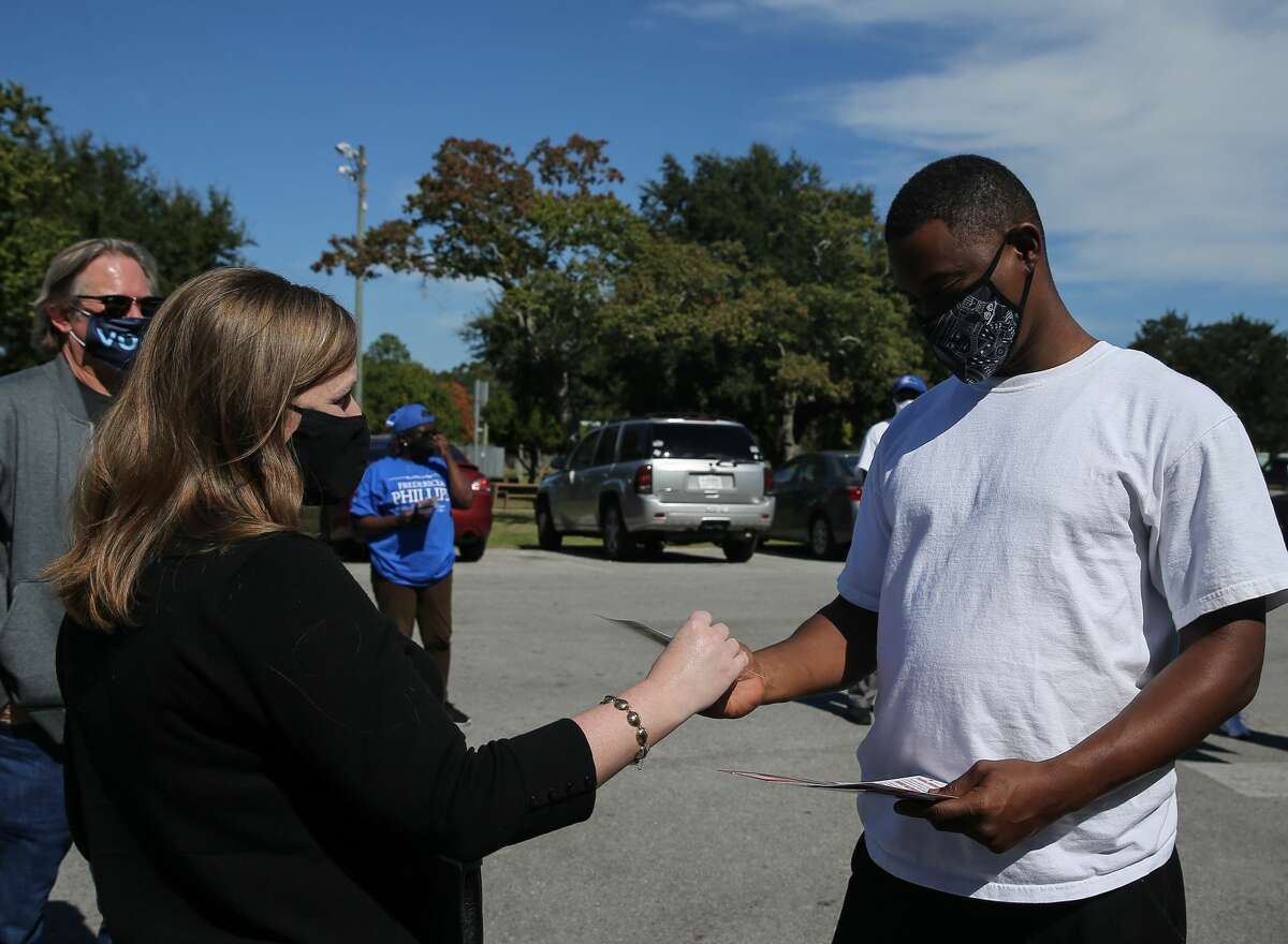 US Congresswoman Lizzie Fletcher greets voter Gregory Coleman Jr. Tuesday, Nov. 3, 2020, at Bayland Community Center in Houston. Fletcher is seeking for reelection.
