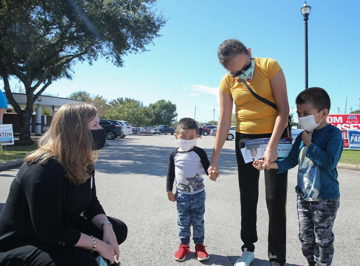US Congresswoman Lizzie Fletcher greets voter Abigail Reyna and her sons, Ethan Reyna 5, and Rooy Reyna, 3, Tuesday, Nov. 3, 2020, at Bayland Community Center in Houston. Fletcher is seeking for reelection.