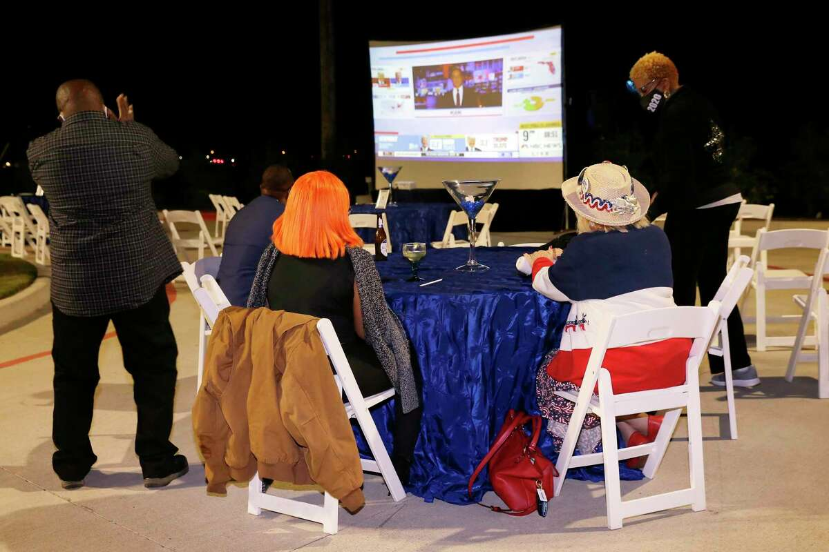 Attendants watch elections results on a big screen TV in the parking lot of Aling's Chinese Bistrow at the watch party for Texas House District 26 candidate Sarah DeMerchant (D), on Tuesday in Sugar Land.