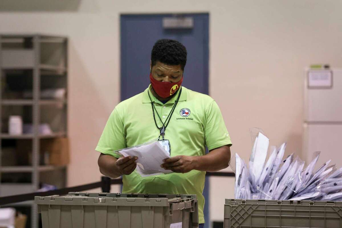 An election worker unloads memory sticks that contain ballots after polls closed Tuesday, Nov. 3, 2020, at NRG Arena in Houston.