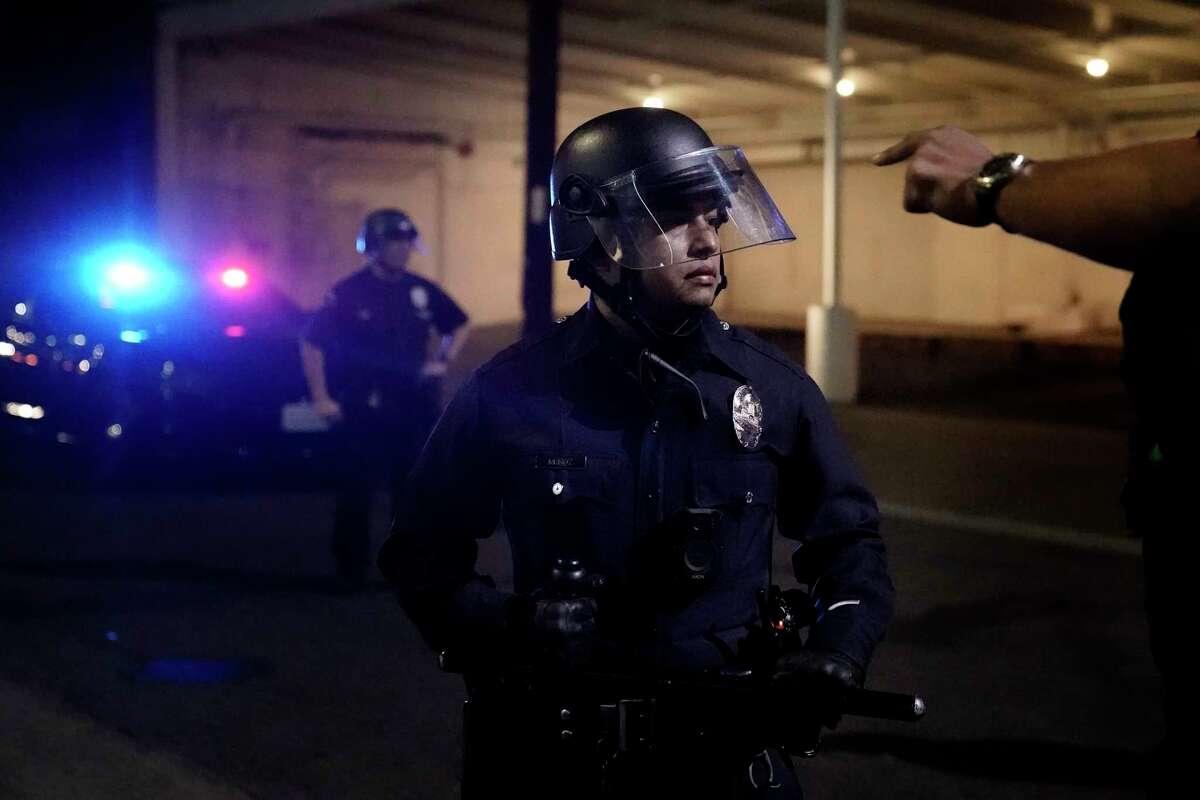 A protestor gestures towards a police official on Election Day, Tuesday, Nov. 3, 2020, in Los Angeles.