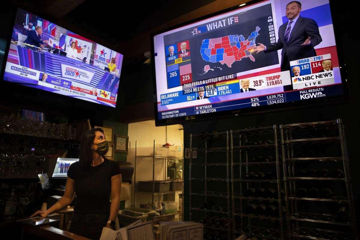 La mesera Sam Schilke sigue los resultados de las elecciones presidenciales de Estados Unidos en un televisor en un bar, el 3 de noviembre de 2020, en Portland, Oregon.
