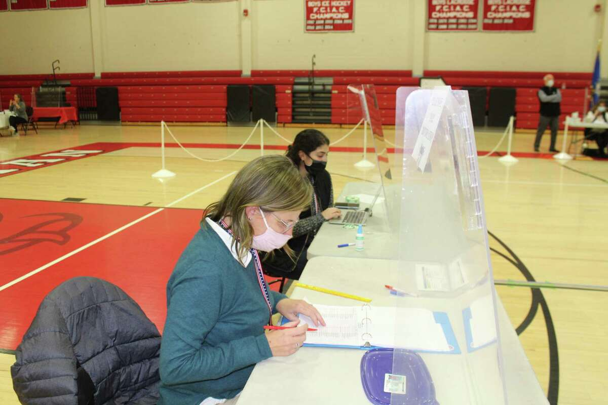 Kelly McCarthy (foreground) and Caroline Ross check a voter's credentials at the polls in the New Canaan High School gymnasium around 5 p.m. Tuesday, Nov. 3.