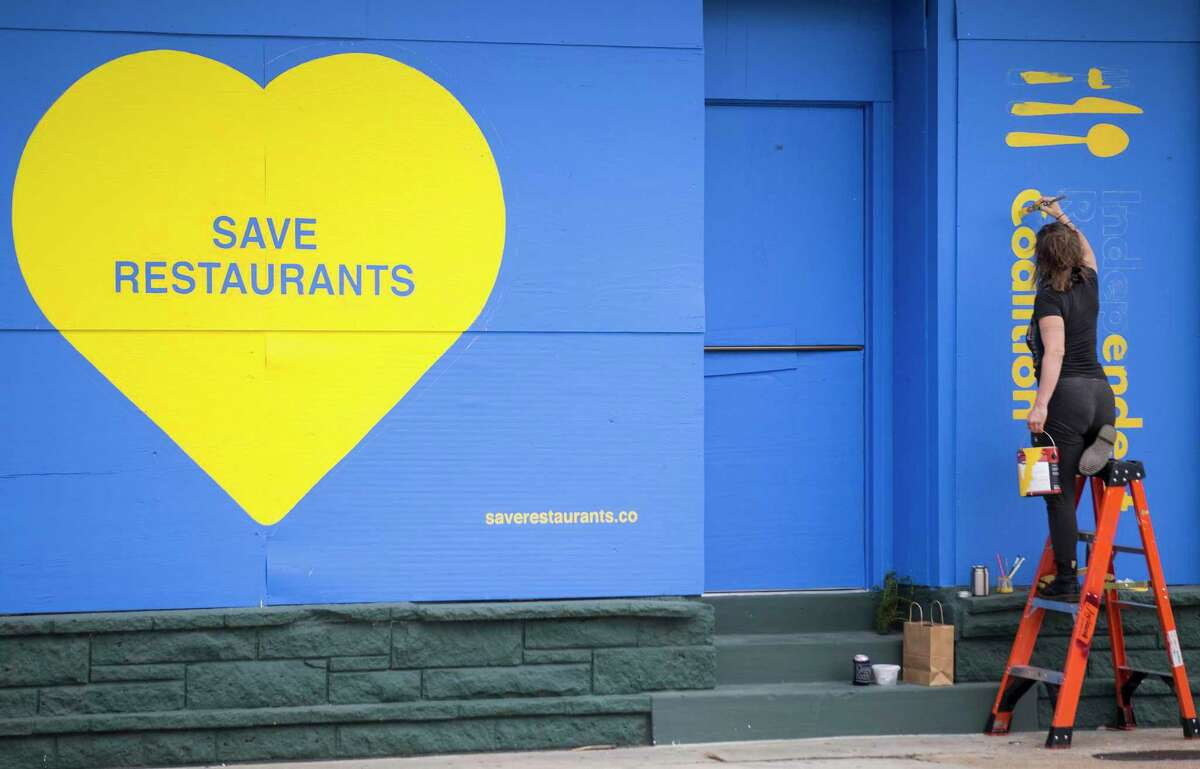 """Traveling sign painter Melissa Eason paints a """"Save Our Restaurants"""" mural on the side of a building on Westheimer for the Independent Restaurant Coalition on Saturday, April 11, 2020 in Houston. Restaurants and bars around the city have closed or have reduced their services due to coronavirus precautions."""