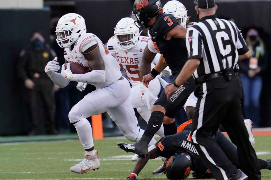 Texas's Joseph Ossai, left, carries a the ball after recovering an Oklahoma State fumble in the second half of an NCAA college football game in Stillwater, Okla., Saturday, Oct. 31, 2020. (AP Photo/Sue Ogrocki) Photo: Sue Ogrocki, STF / Associated Press / Copyright 2020 The Associated Press. All rights reserved.