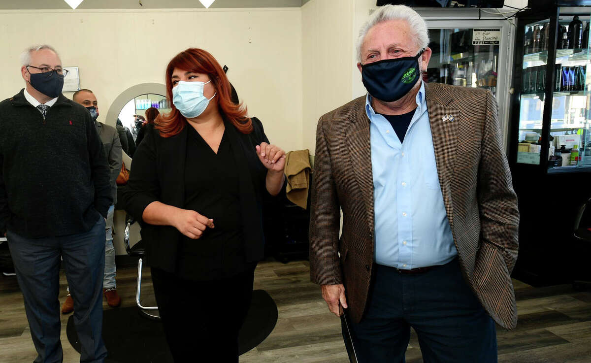 The International Beauty Academy founder Martha Interiano celebrates the grand opening with Norwalk Mayor Harry Rilling, right, Wednesday, November 3, 2020, at Krystal Hair Designers in Norwalk, Conn. The city is monitoring the coronavirus situation to determine if closures are needed. The state reverted back to reopening Phase 2.1, which limits business capacity, but it's up to the city to close businesses and schools. Mayor Harry Rilling said the city is monitoring the situation and trying to determine what's causing the increase in cases. If they're traced back to businesses, closures may be necessary. 'It's very challenging because many of the businesses, when we first went into ... a lockdown, they struggled,