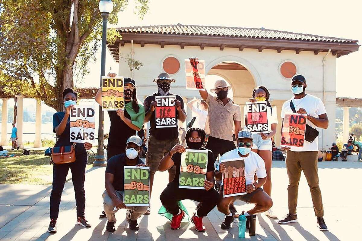 Participants from Simileoluwa Adebajo's #EndSars gathering in Oakland on Oct. 24 hold signs in support of the Nigeria-based movement.