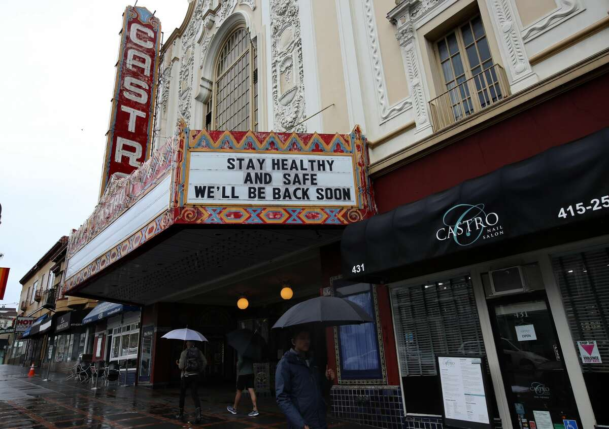 Pedestrians walk by the Castro Theatre just after it closed as a result of the pandemic on Mar. 15, 2020.