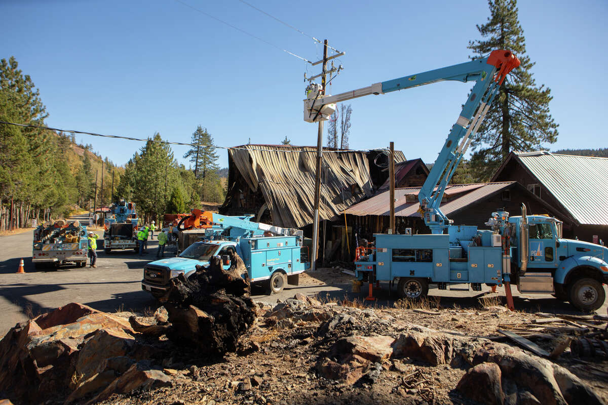 A PG&E crew works on power lines above the burned remains of the Cisco Grove Store.