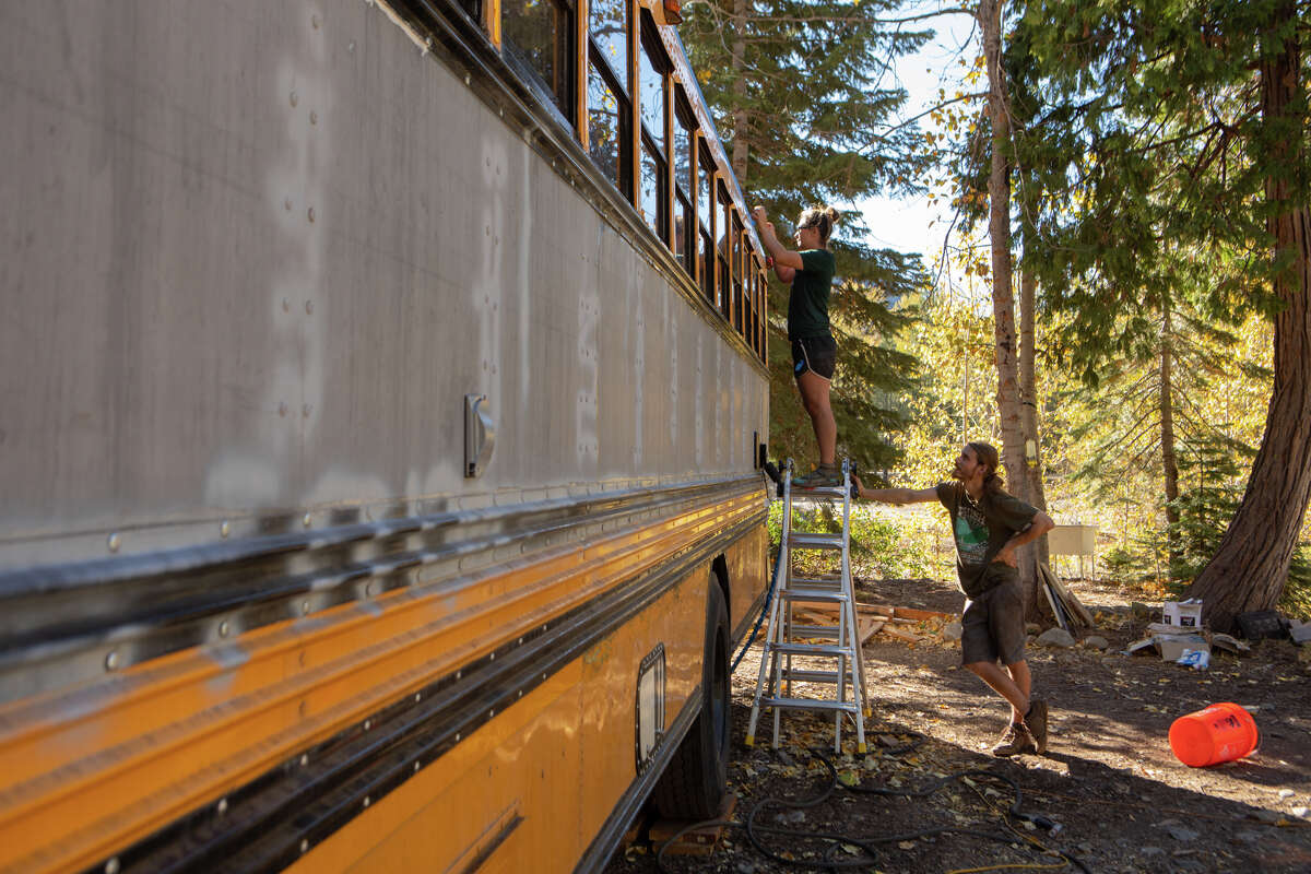 Chelsea Reeser and Robert Washburn put a coat of paint in their school bus before winter. They are one of the many residents of the Cisco Grove Campground.