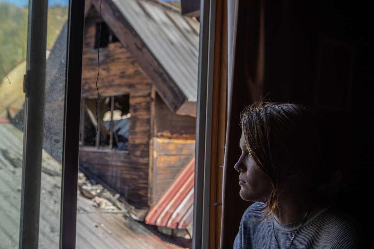Ashtyn Rich looks out of her bedroom window at the charred remains of the general store. She awoke from sleep only to see a wall of flames just feet away from her bed.