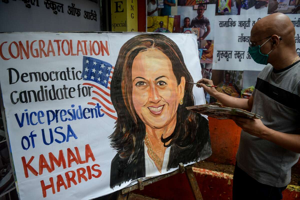An art enthusiast paints the likeness of Kamala Harris on a poster outside a drawing school in Mumbai on Aug. 13, 2020.