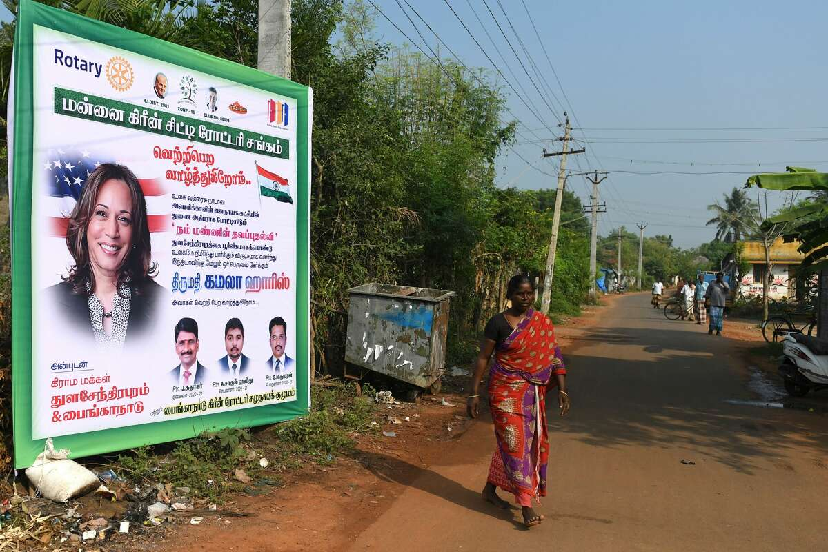 A woman walks past a poster of Democratic vice presidential candidate Kamala Harris at her ancestral home of Thulasendrapuram in the southern Indian state of Tamil Nadu.