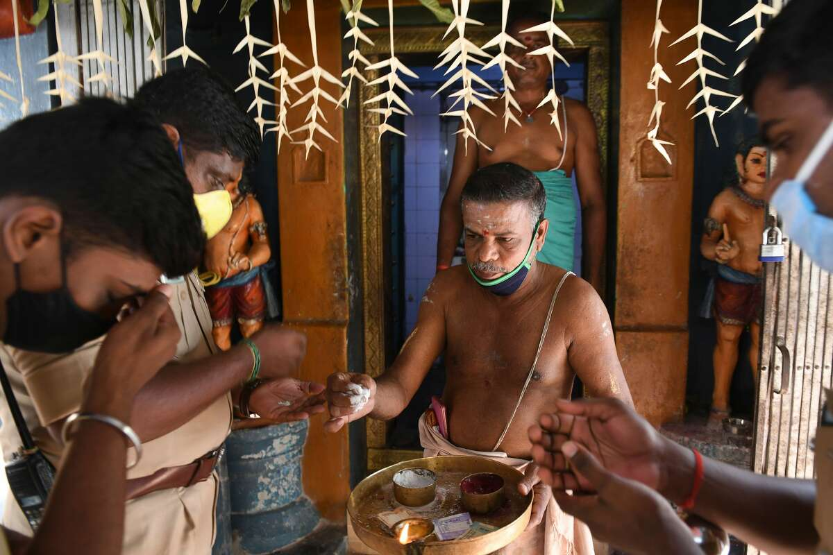 A temple priest gives holy ashes to residents as they offer prayers for U.S. Democratic vice presidential candidate Kamala Harris, at her ancestral home of Thulasendrapuram in the southern Indian state of Tamil Nadu on Nov. 3, 2020.