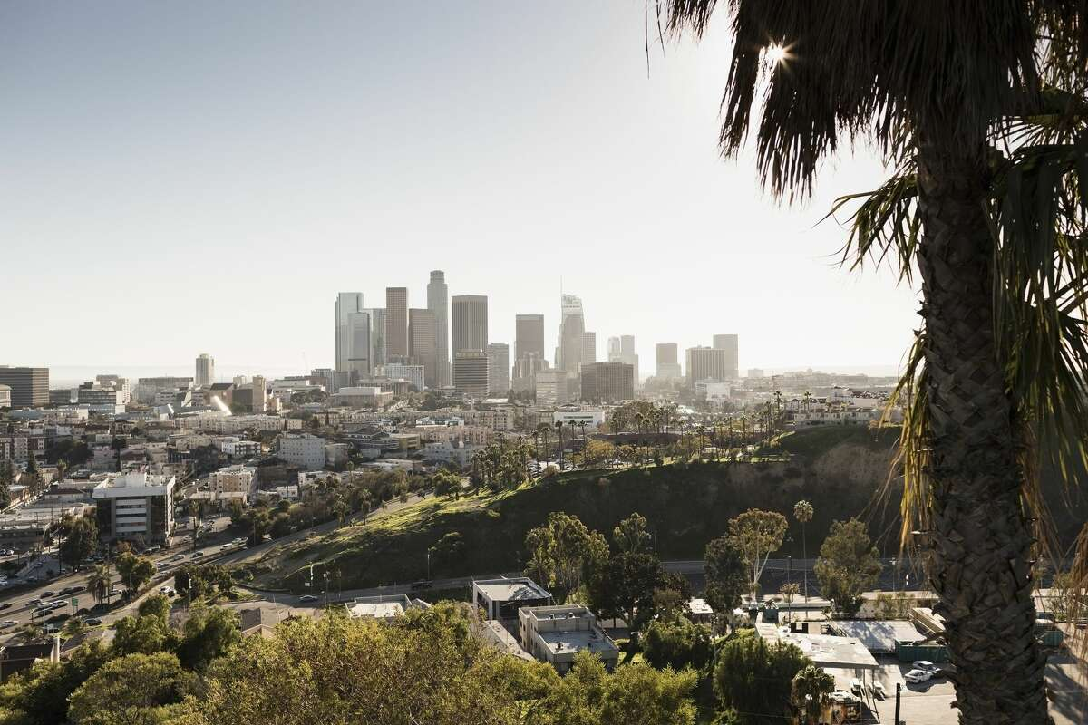 The Los Angeles skyline rises in the distance.