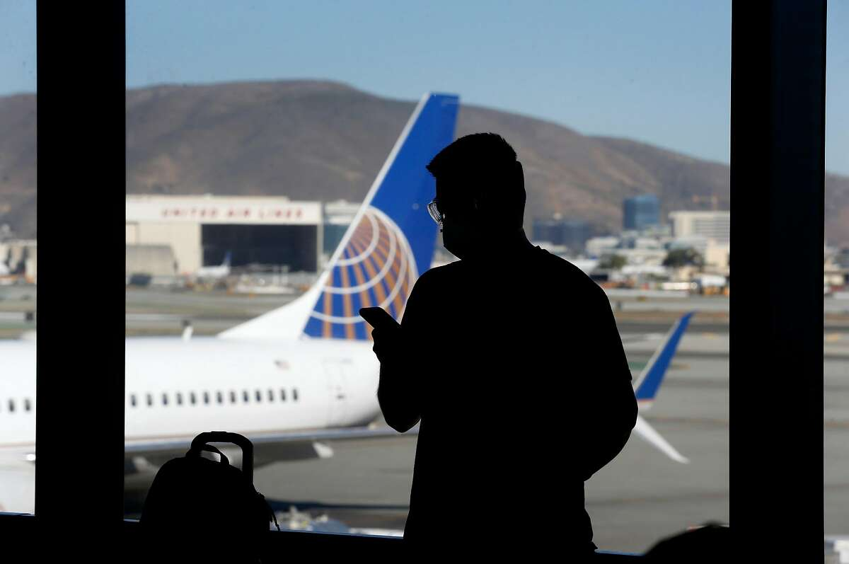 A traveler checks his mobile phone while waiting to board a United flight to Honolulu at SFO in San Francisco, Calif. on Thursday, Oct. 15, 2020. As the airline industry sees a modest rise in travel, a rapid COVID-19 testing site has been set up at the airport to provide travelers with documentation of test results to present upon arrival at their final destinations.