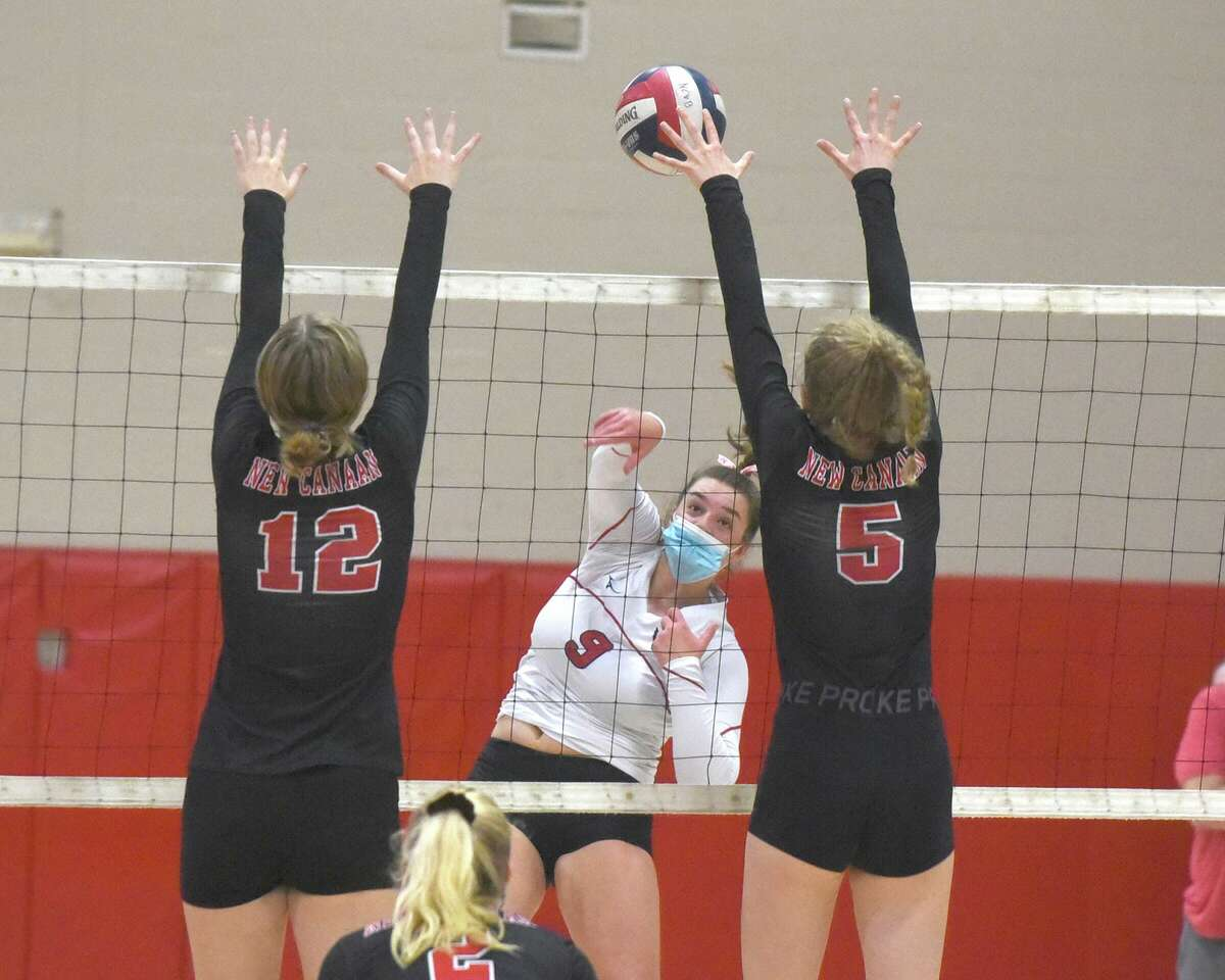 Greenwich's Lilly Saleeby (9) takes a shot as New Canaan's Lillie Gray (12) and Lindsay Mulchahy (5) try to block during a girls volleyball contest at New Canaan High School on Thursday, Oct. 22, 2020.