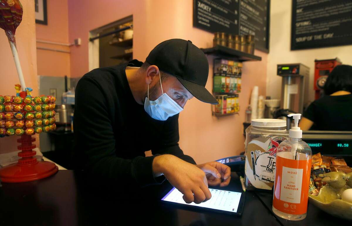 Cafe Encore owner Hamel Belayadi confirms an incoming order placed on the DoorDash platform in San Francisco, Calif. on Wednesday, Nov. 4, 2020. California voters passed Prop. 22 which will allow drivers for ride-hail and delivery services to remain independent contractors for companies such as Uber, Lyft and DoorDash.