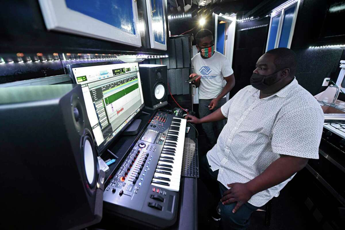 David Gordon, right, works on the music tracks as Dauda Mohamed Hanneh of Albany, left, thinks of words to go with the song they are working on in the lyricism studio parked at Hannaford on Tuesday, Oct. 20, 2020 in Albany, N.Y. Gordon built the studio in the RV as a mobile extension of the lyricism program at the Boys & Girls Club of the Capital Region to help local youth make music. (Lori Van Buren/Times Union)
