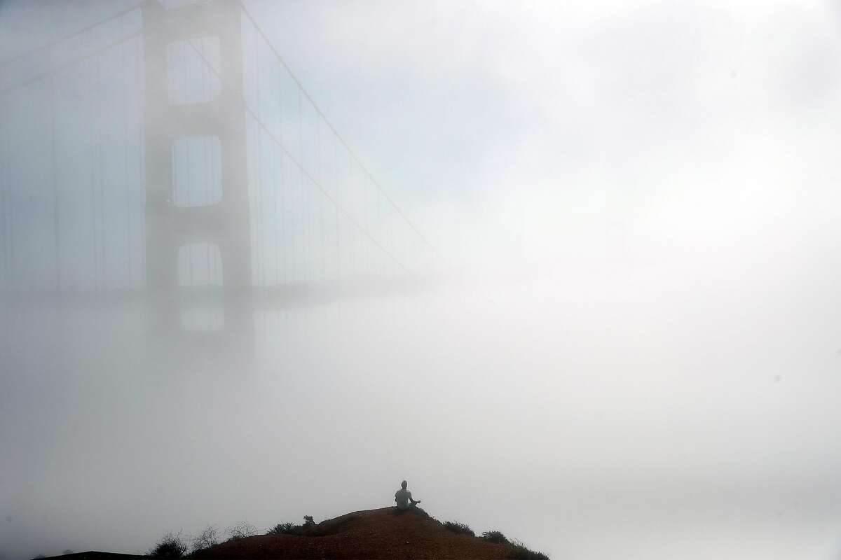 With the fog shrouded Golden Gate Bridge in front of him, Ivan Gushchin of Citrus Heights meditates at Marin Headlands in Sausalito, Calif., on Monday, October 19, 2020.