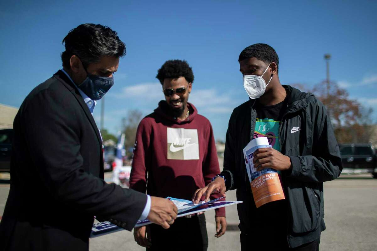 Democrat Sri Kulkarni talks to voters KP, 21, and Avery Crucial, right, 20, at a polling site on Tuesday, Nov. 3, 2020, in Houston. Kulkarni lost his bid for Texas' 22nd Congressional District to Republican Fort Bend County Sheriff Troy Nehls.