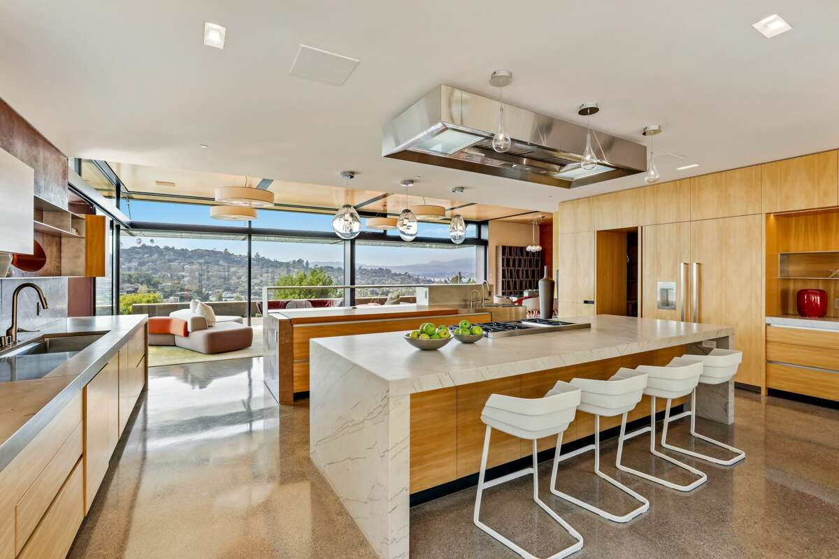 There is an open flow from the modern kitchen to outside dining with a view.