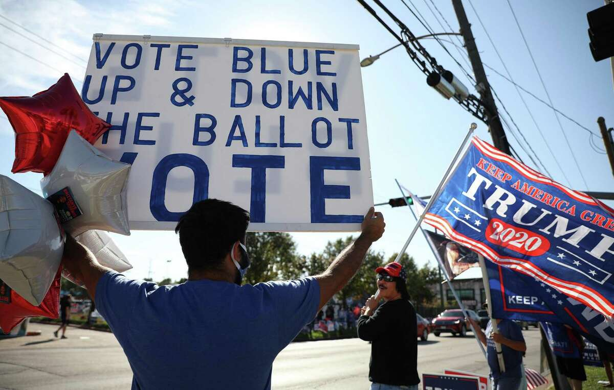 A person holds a sign in support of Democrats, left, next a person waving a flag in support of U.S. President Donald Trump outside at a polling location for the 2020 Presidential election in Houston, Texas, U.S., on Tuesday, Nov. 3, 2020. American voters, at least those who've not yet cast ballots, go to the polls Tuesday to choose between PresidentDonald Trumpand Democratic nomineeJoe Bidenand cast votes in U.S. House and Senate races and state and local elections. Photographer: Sharon Steinmann/Bloomberg