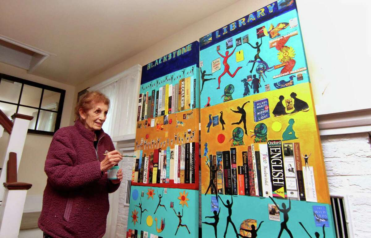 Artist Martha Resnikov puts the finishing touches one of two doors she painted for the upcoming exhibit The Painted Doors of Branford in Branford. Resnikov's two doors, commissioned by the Friends of the Blackstone Library, celebrate the magic of books with painted paper collage.