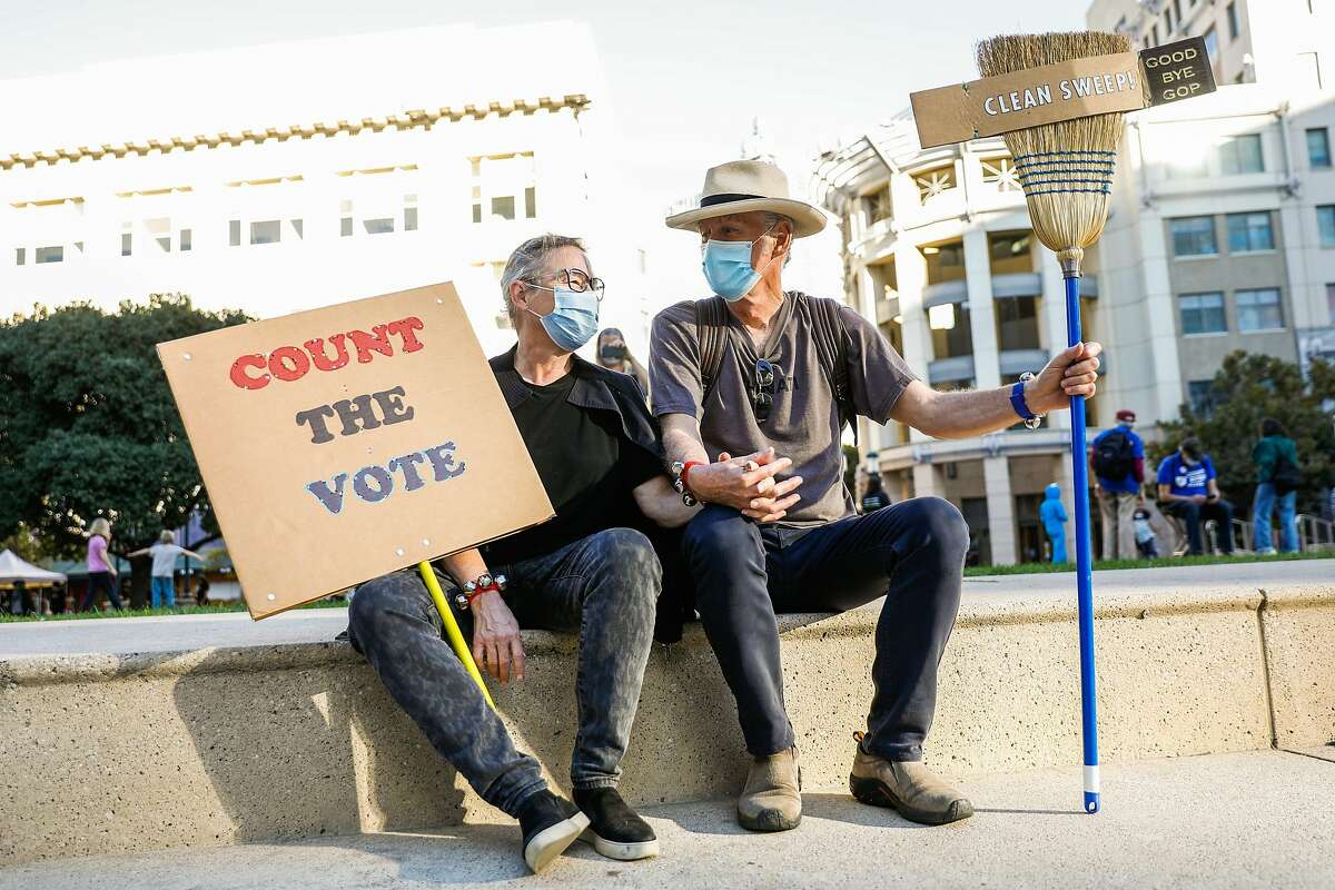 Dana Buntrock (left) and Leroy Howard hold hands during the Defend Our Democracy: Count Every Vote event held at Frank Ogawa Plaza in Oakland on Nov. 4.