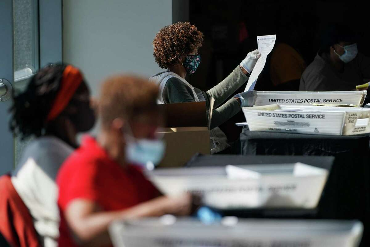 Election officials wearing protective masks count absentee bal- lots for the presidential election in Atlanta, Ga., on Wednesday.