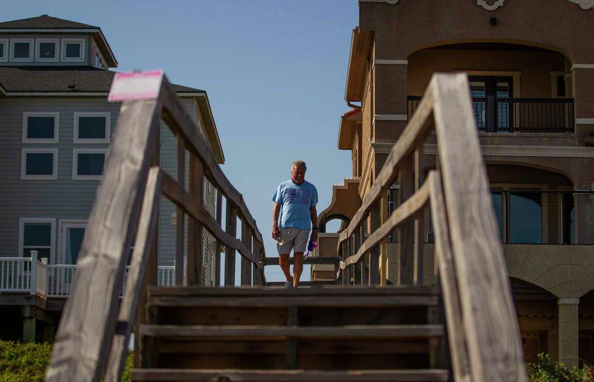 Michael Wilhelm crosses a wooden bridge from his home to the beach near the site of a planned pipeline by Enterprise and Enbridge in Surfside, TX, Friday, Oct. 2, 2020. Residents of the city and the city's government oppose the pipeline that would allow crude oil to travel across Follet's Island to an offshore terminal where the oil could be exported directly into waiting tankers. Residents are worried about possible impacts to the environment and the aquifer that the city relies on for their water supply.