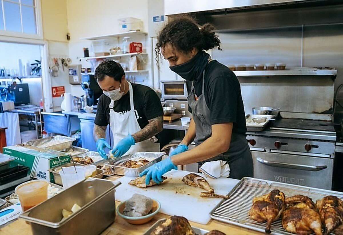 Keone Koki (left) and Bilal Ali prepare chicken for takeout meals under the name Michoz at the Hidden Cafe in Berkeley, their latest project after their pop-up in West Oakland was shut down.