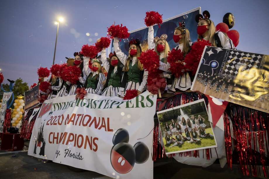 The Woodlands High School Highsteppers wave at passing crowds of families during the annual Red and Green parade and pep rally outside Woodforest Bank Stadium in Shenandoah, Wednesday, Nov. 14, 2020. A variety of student organizations created themed floats that were on display during the first hour of the rally. Photo: Gustavo Huerta/Staff Photographer / 2020 © Houston Chronicle