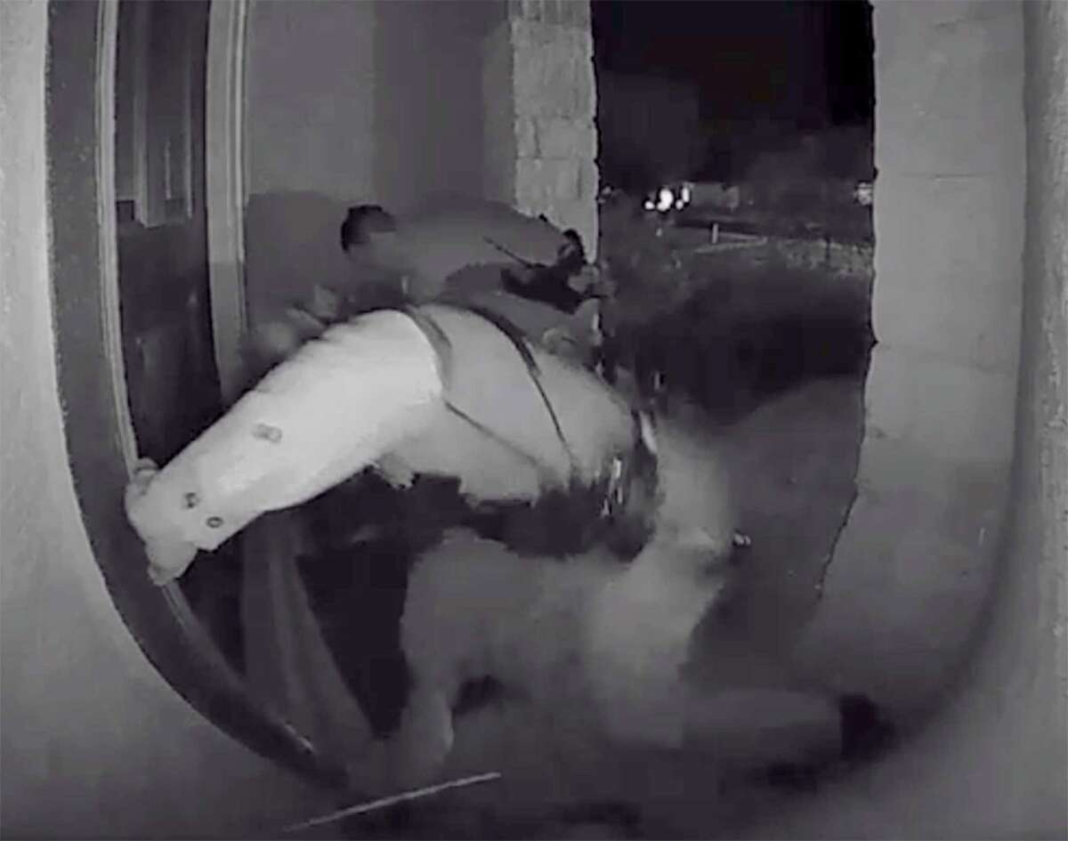 Screen grabs from a home surveillance video show a Schertz police officer kicking Zekee Rayford, 18, on the front steps of his home.