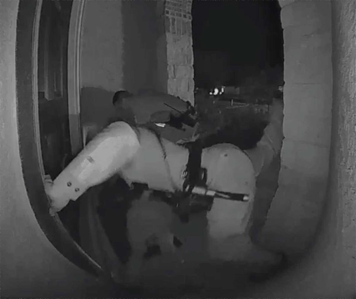 A screen grab from a home surveillance video shows a female Schertz police officer with her leg extended, preparing to kick Zekee Rayford, 18, with her knee on the front steps of his home while the parents watch from inside the front door.