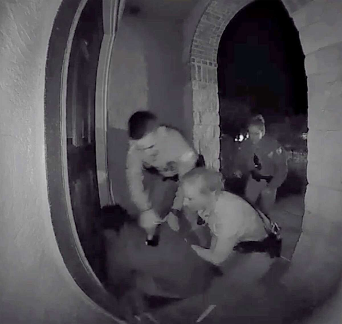 A screen grab from a home surveillance video shows Schertz police officers tasing and forcibly restraining Zekee Rayford, 18, on the front steps of his home.
