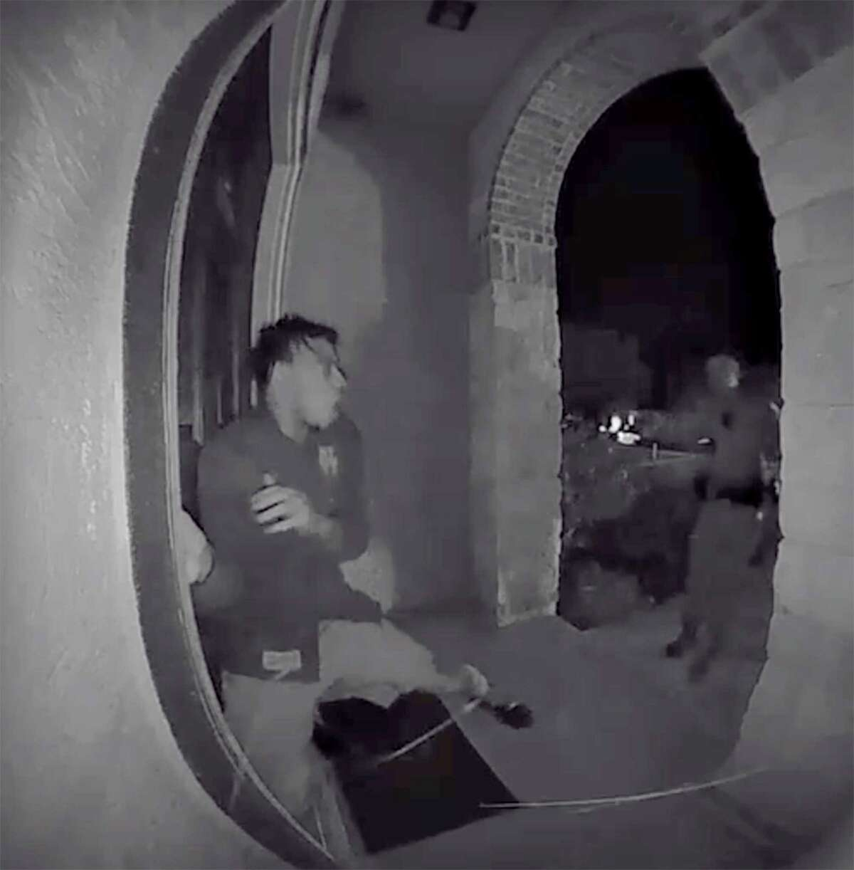 A screen grab from a home surveillance video shows a Schertz police officer pointing a weapon at Zekee Rayford, 18, before arresting him on the front steps of his home while the parents watch from inside the front door.