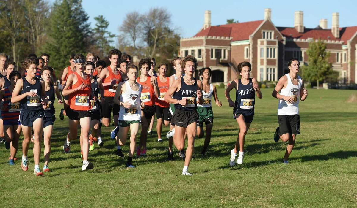 Runners pass in front of New Canaan's Waveny House near the start of the FCIAC East boys cross country race in Waveny Park on Wednesday, Nov, 4, 2020.