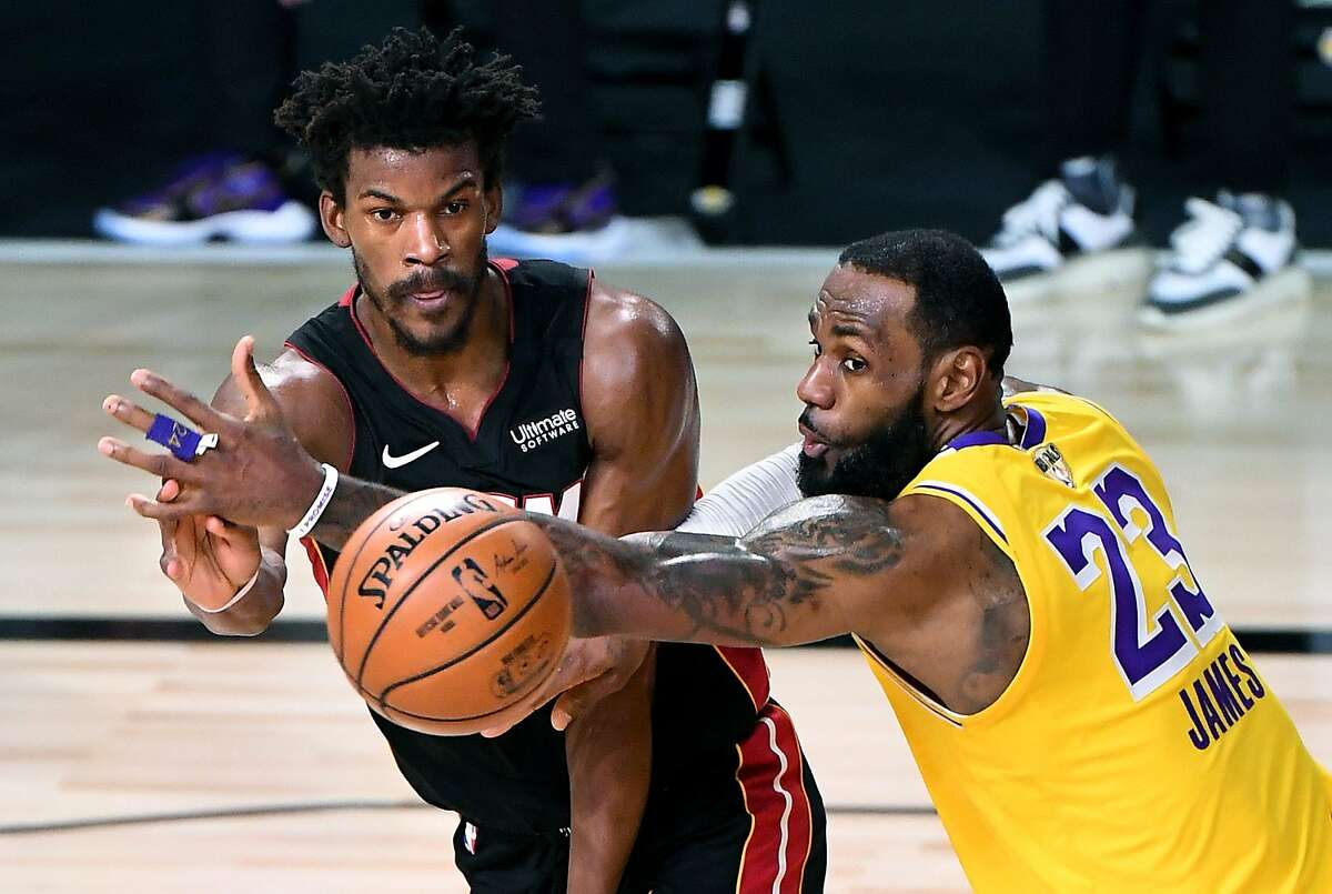 ORLANDO, FLORIDA OCTOBER 6, 2020-Lakers LeBron James tries to break up a pass from Heat's Jimmy Butler in the 4th quarter in Game 4 of the NBA FInals in Orlando. (Wally Skalij/Los Angeles Times/TNS)