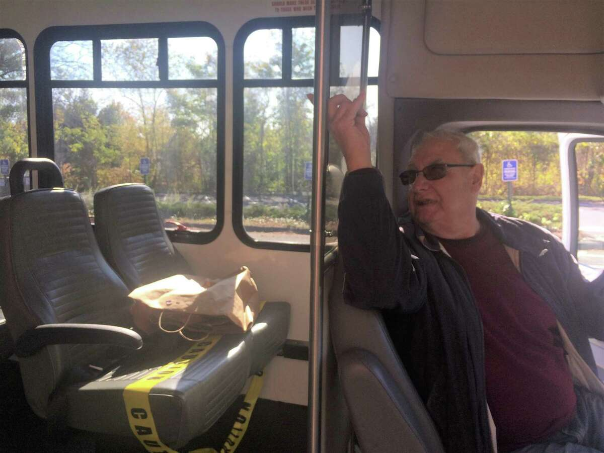 Bill Schiappa raps on the Plexiglass shield that has been installed between the passengers and driver on a Trumbull Senior Center transportation van.