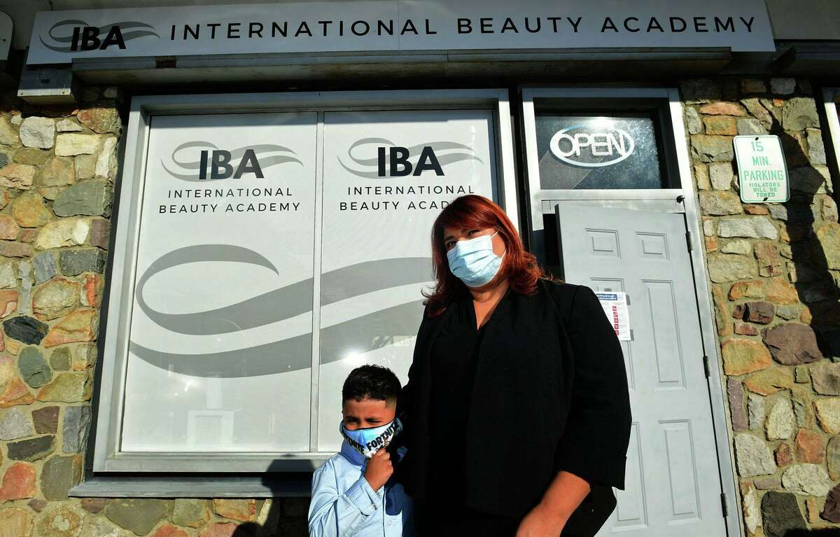 The International Beauty Academy founder Martha Interiano celebrates the grand opening with her son Kayden Duron, 5, Wednesday, November 3, 2020, at Krystal Hair Designers in Norwalk, Conn.