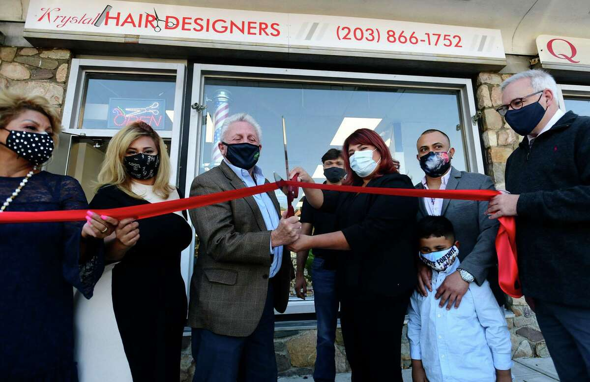 The International Beauty Academy founder Martha Interiano, center, celebrates the grand opening with Norwalk Mayor Harry Rilling, center left, and family and associates Wednesday, November 3, 2020, at Krystal Hair Designers in Norwalk, Conn. The International Beauty Academy held its grand opening on Wednesday, though founder Martha Interiano said she anticipates they won't be taking students for enrollment until January. The opening of the school already had to be pushed back due to the pandemic. Interiano has run Krystal Hair Designers on North Main Street for 25 years. During that time, many of her Hispanic clients have said they'd like to go to beauty school, but there weren't any with courses taught in Spanish.