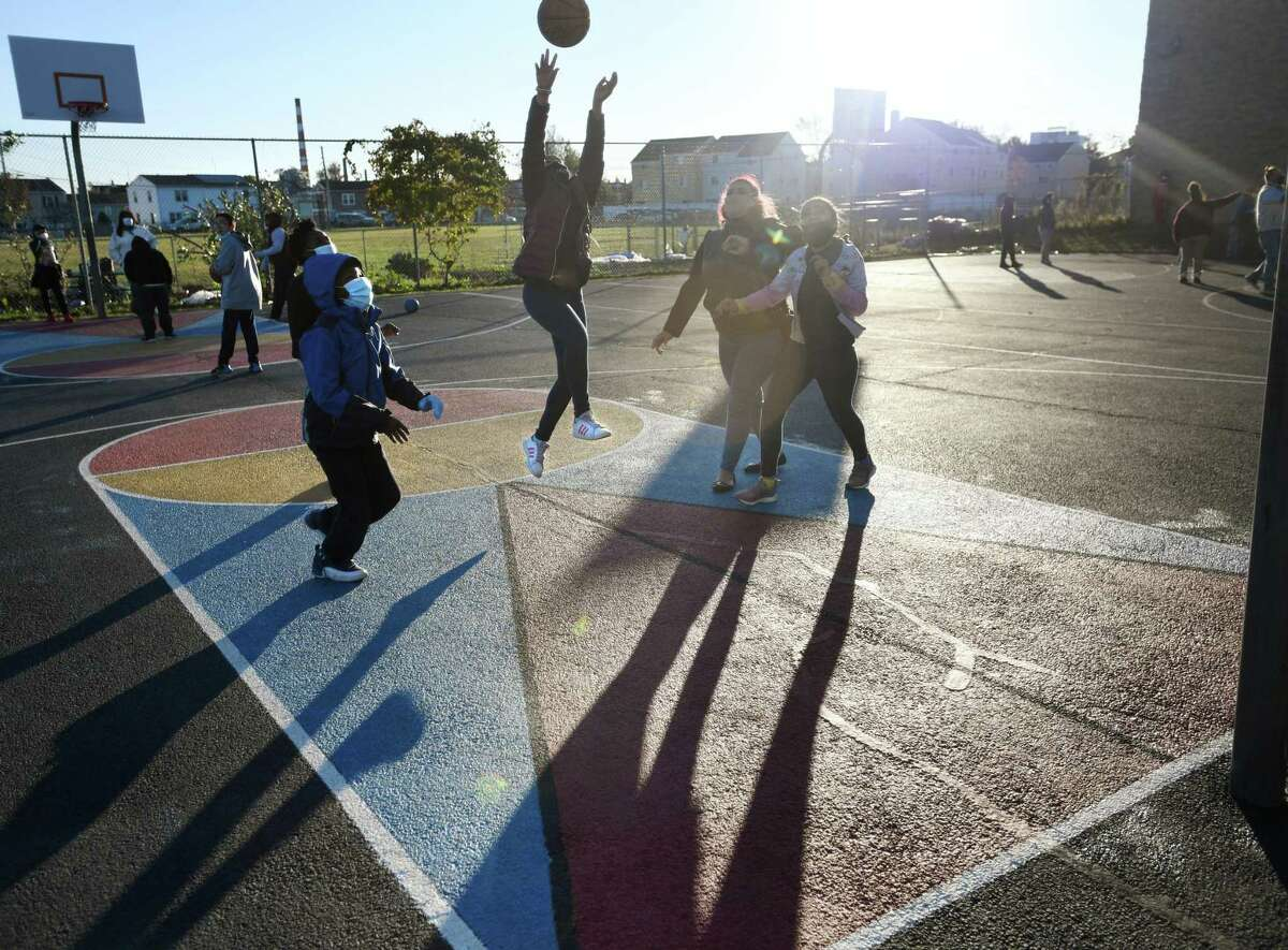 Students have fun with a game of basketball on the playground during the afterschool program at Barnum and Waltersville Schools in Bridgeport, Conn. on Monday, November 2, 2020.