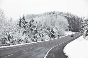Diminishing perspective view of a rural highway with a small car speeding up the hill in the Adirondacks Mountains region of northern New York State during a heavy snow storm.