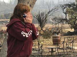 """FILE - In this Sept. 30, 2020, file photo, Nikki Conant cries as she looks at the debris of her home and business, """"Conants Wine Barrel Creations,"""" after the Glass/Shady fire completely engulfed it in Santa Rosa, Calif. A new generation of California voters is being asked to roll back affirmative action and property tax laws put in place decades ago in an election that will test the boundaries of the state's left-leaning politics. Voters are being asked to unspool part of landmark Proposition 13, the 1970s law that set strict limits on property tax increases and fueled a national tax revolt. (AP Photo/Haven Daley, File)"""