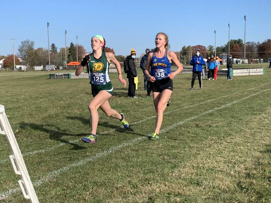Dow High's Katie Watkins (left) sprints toward the finish line in a Division 1 regional held at White Pine Middle School on Oct. 31, 2020. Photo: Daily News File Photo